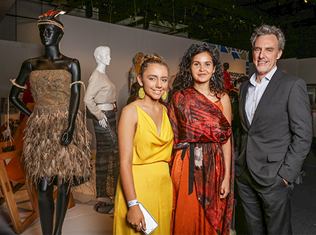 A female student has designed an interpretation of an australian indgenous possum cloak and is pictured at the opening night of an exhibition with a woman from the indigenous art community and ceo of the vcaa