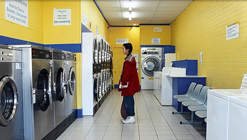 A young woman in a red coat stands in a colourful Laundromat with a blank expression