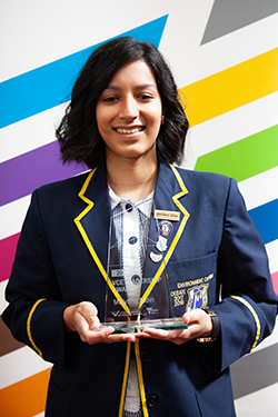 young woman with short hair smiling holding her trophy prize