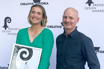 a young woman smiling and holding a certificate and a man standing next to her both are in front of a creative victoria sign