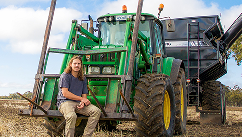 A male VET Agriculture student sitting in front of harvester machine